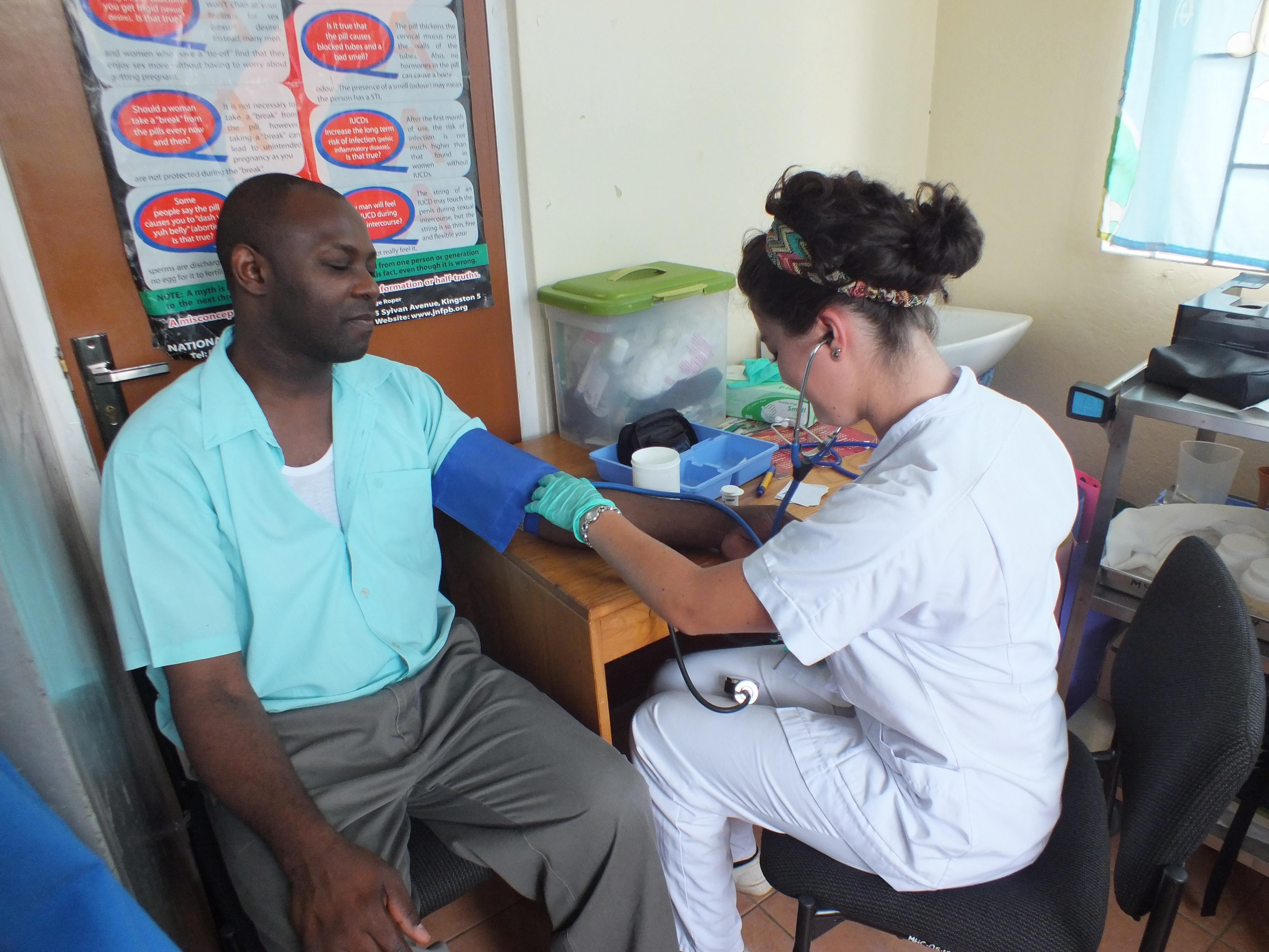 Female medical intern takes a local man's blood pressure in a Health Centre during a medical outreach in Jamaica.